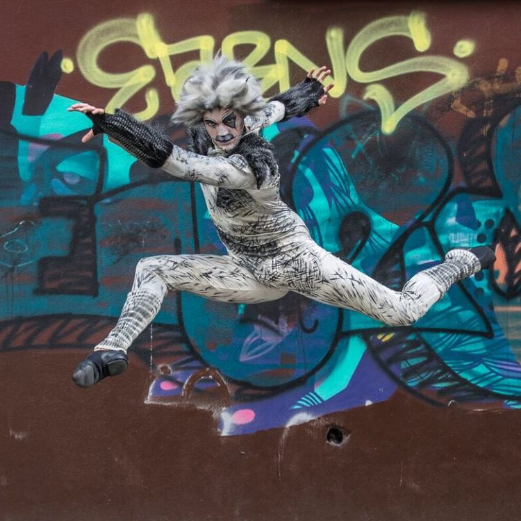 Cats the Musical cast member jumps in front graffiti wall
