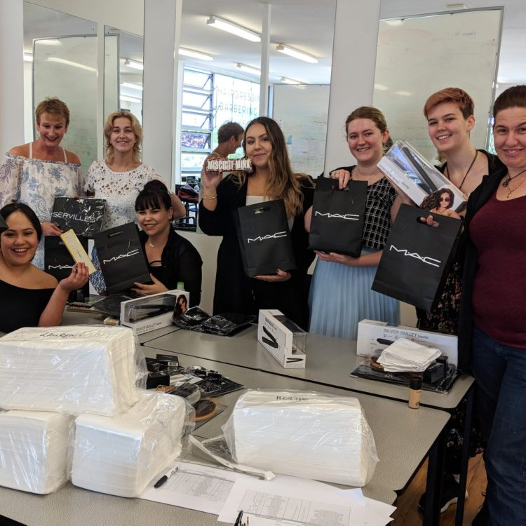 Level 4 makeup artist students pose with Mac course kits