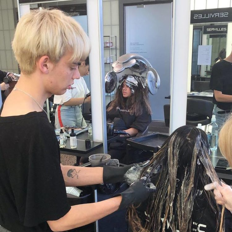 Hairdressing student dyes long hair at Academy Salon