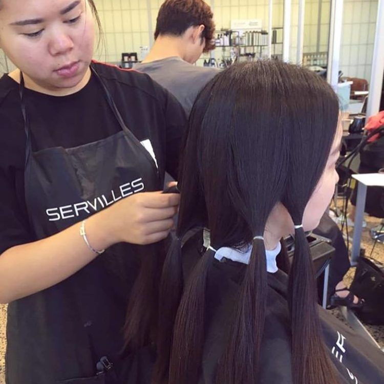 Hairdressing student prepares hair for donation