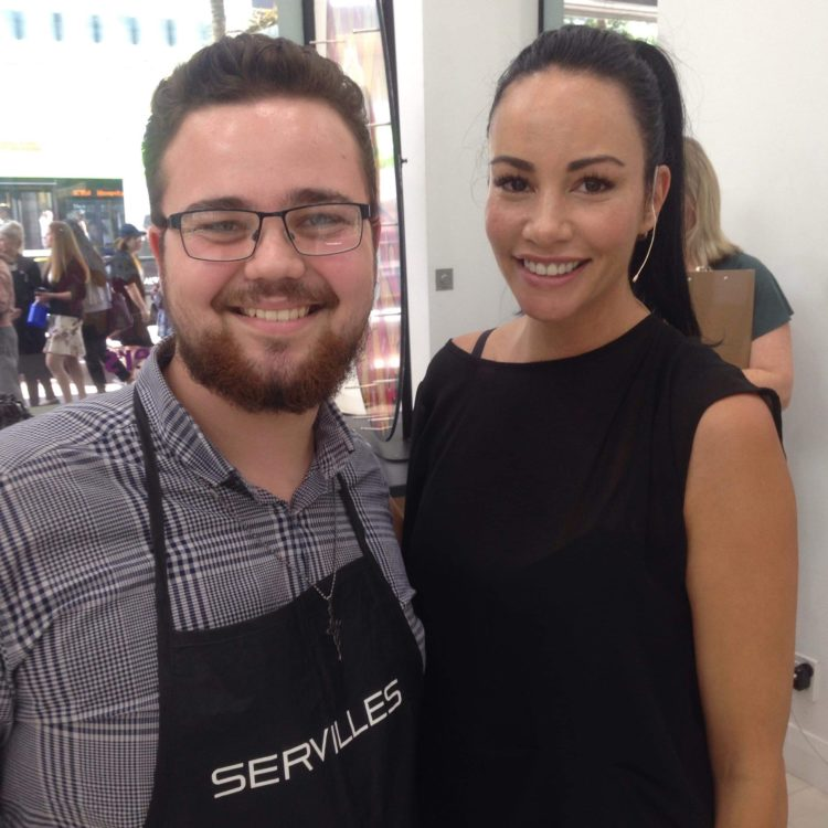 Barbering student poses with TV personality