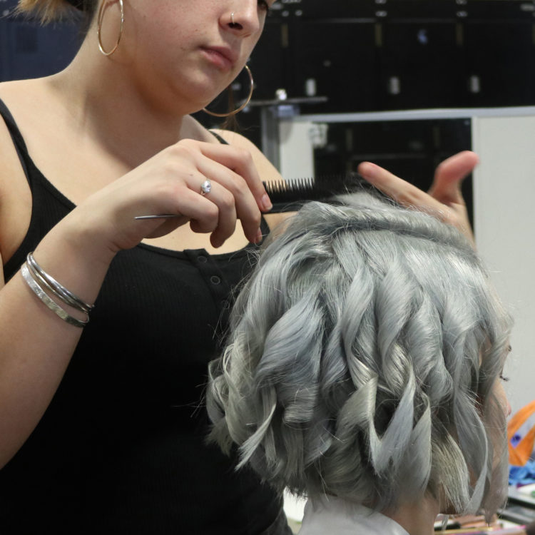 Hairdressing student preps model with steel coloured hair