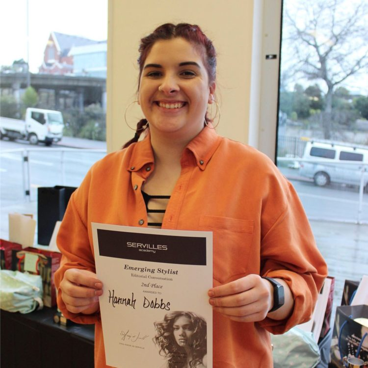 Emerging Stylist Hannah stands with certificate
