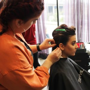 Hairdressing student clips hair up in Salon