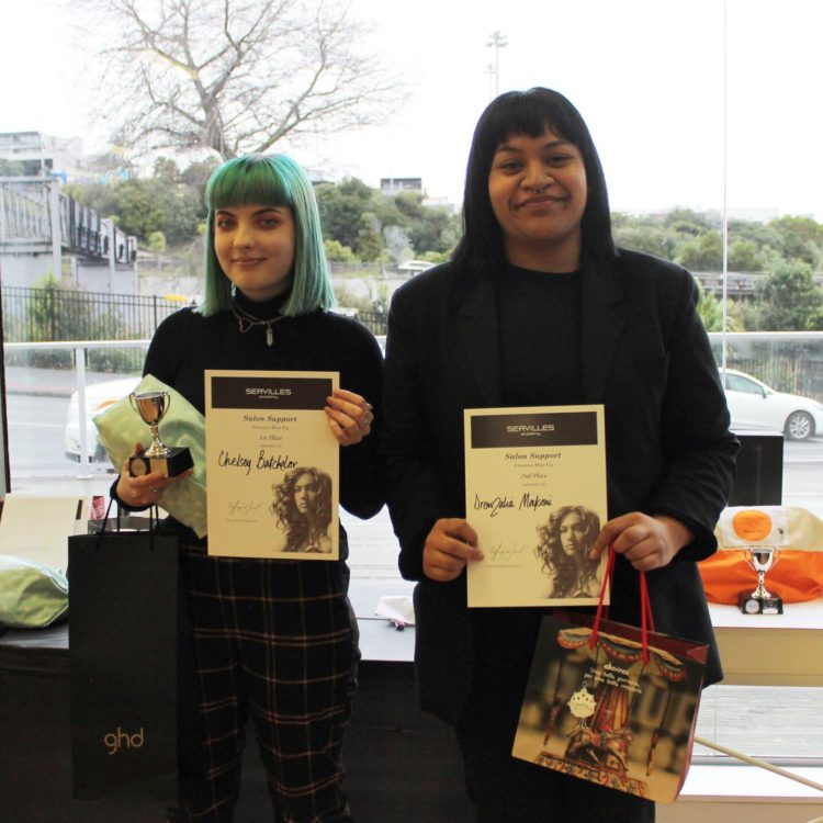 Two Servilles students standing with certificates and prizes