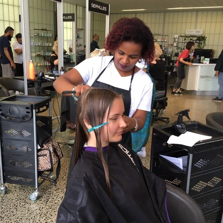 Servilles hairdressing student colours hair