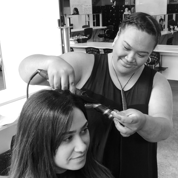Tutor Chanelle curls hair at Servilles Academy
