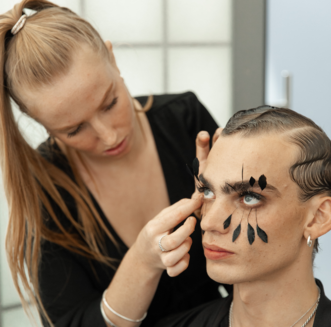 Makeup student applies feathers to young male