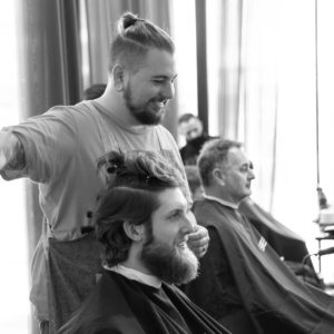 Barber student stands next to client