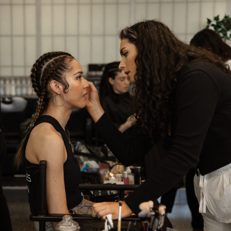 Young woman with braids gets makeup applied