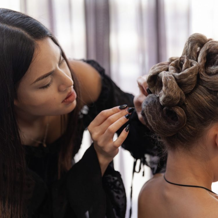 Hairdressing student places bobby pins in hairstyle