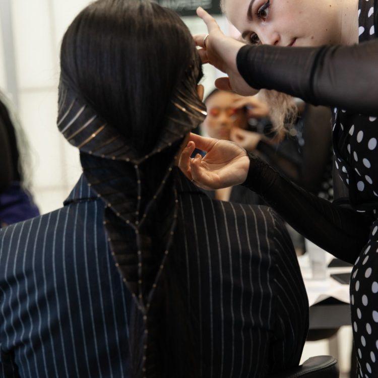 Girl with hair clips gets makeup applied
