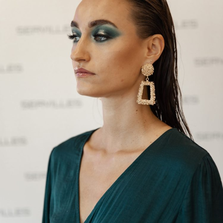 Brunette female with emerald eyeshadow and dress