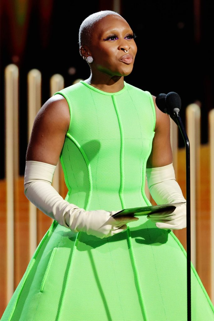 A person in a green dress  Description automatically generated with medium confidence