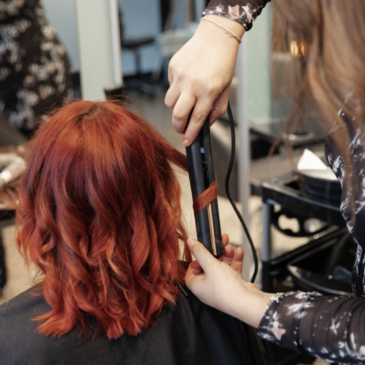 Hairdressing student curling red hair